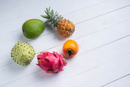 Exotic fresh summer fruits on white background. Dragon fruit, pineapple, persimmon, mango, annona cherimola flat lay with free copy space.