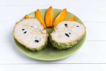 Fresh exotic tropical fruit. Two halfs of custard apple isolated on white background, annona cherimoya.