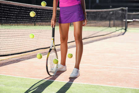 Close up of stunning woman legs with racket near and a lot of falling tennis balls on the background of outdoor court. Dolly shot.