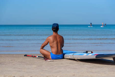 Tanned man sits on the beach of the sea near his surfboard and looks to the sea. The concept is a sporty and healthy lifestyle.