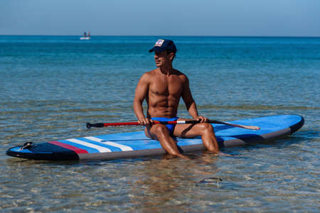 Tanned sporty man sits on his surfboard on the water and looks to the sea. The concept is a sporty and healthy lifestyle.