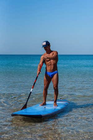 Une personne sportive en bonne santé se tient sur sa planche de surf sur l'eau et rame à la rame. Le concept de mode de vie sportif et sain. Banque d'images