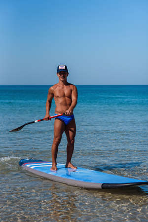 Tanned sporty man in a cap stands on his surfboard on the water holding in the hands an oar and looks into the sea. The concept is a sporty and healthy lifestyle. Banco de Imagens
