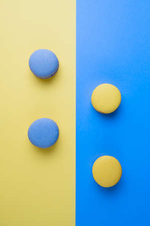 Sweet tasty blue and yellow french macaron cakes on yellow and blue background.