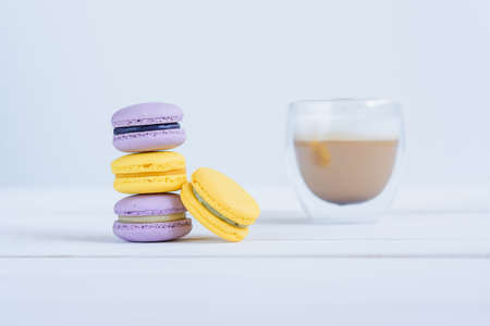 Tasty violet and yellow macarons and cup of latte on white wooden background. Stockfoto