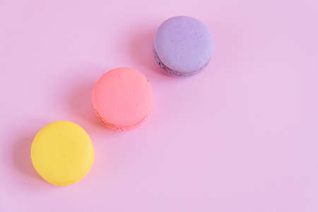 Tasty violet, pink and yellow french macaron cakes on pink background.