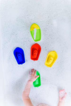 Plastic multicolored toy boats on foam bath.
