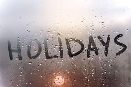 the inscription holidays on the sweaty glass.