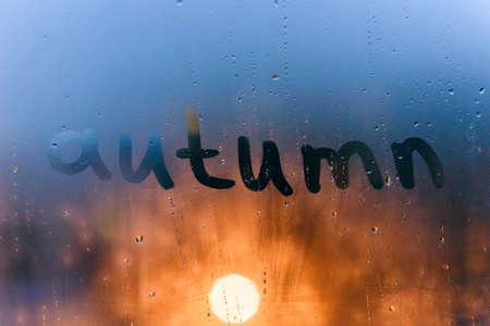 Rainy weather, the inscription autumn on the sweaty glass 写真素材