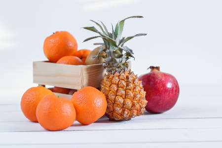 Group of fresh tropical fruits in small wooden box.