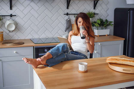 Cheerful pretty woman using tablet computer and drinking coffee on the kitchen at home.