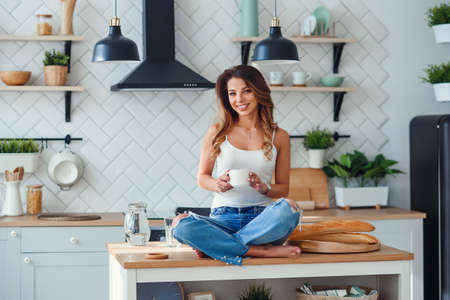 Pretty happy woman drinks coffee while sitting on the table on the cozy kitchen in the morning at home. Morning relaxation at home.