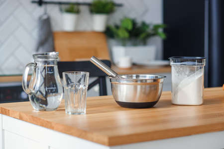 Kitchen utensils for dough preparation. A bank with water, a metal plate and a flour.