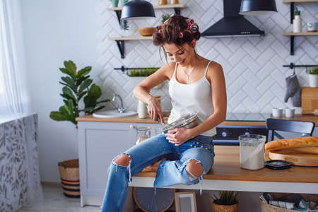 Beautiful smiling woman in casual clothes kneads a dough in a metal plate at stylish kitchen. Young pretty woman baking on bright home kitchen. Stockfoto - 123070123