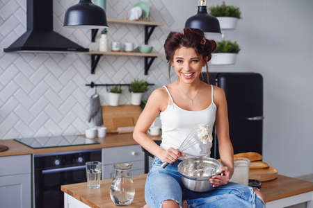 Beautiful smiling woman in casual clothes kneads a dough in a metal plate at stylish kitchen. Young pretty woman baking on bright home kitchen.