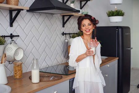 Beautiful woman drink milk at the breakfast, in the stylish cozy kitchen. Healthy eating and diet concept.