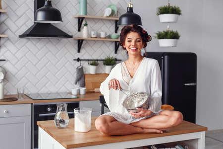 Attractive girl in white bathrobe having fun while preparing dough at stylish modern kitchen. Young pretty woman baking on cozy kitchen.
