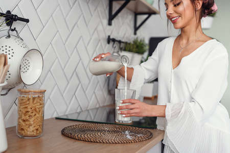 Beautiful smiling woman pours fresh milk from a carafe into a glass, in the stylish cozy kitchen at the morning. Healthy eating and diet concept. Stock Photo