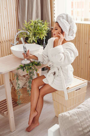 Pretty young girl with a white towel on head dressed in bathrobe looks at herself in the mirror in cozy bathroom after morning shower.