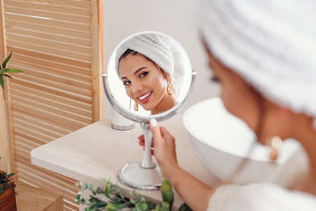 Attractive young woman with a white towel on her head dressed in bathrobe looks at herself in the mirror in stylish bathroom after morning shower. 写真素材