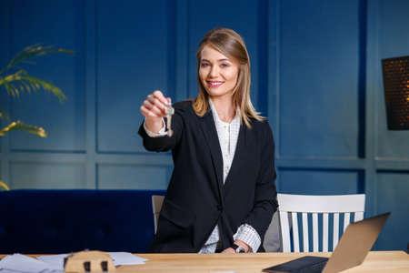 Smiling female realtor gives keys on blue background.