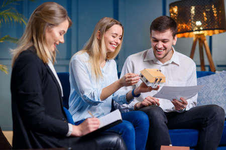 Happy young couple discussing 3d model and sketch of future house with designer.