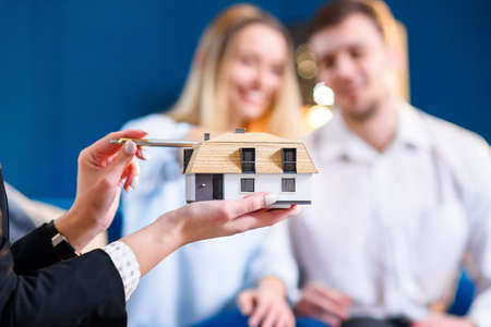 Close up of female hands holding 3d model of house. Stockfoto
