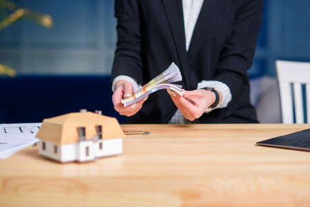 Female real estate agent hands counting money after successful deal for buying house.
