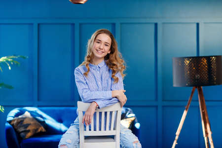 Beautiful stylish girl in casual clothes sits on a white wooden chair in stylish modern interior with blue background. Stockfoto