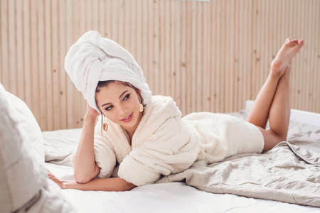 Seductive smiling young woman lying on the bed at home after morning spa rpocedures dressed in white bathrobe. Beautiful girl having relax on the bedroom in morning.