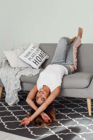 Beautiful woman relaxing on a grey couch with head upside down. Cute girl having fun at cozy home in lazy day.