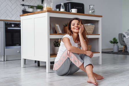 Cute girl sitting on the floor on the background of stylish kitchen. Womens housework concept. Stockfoto