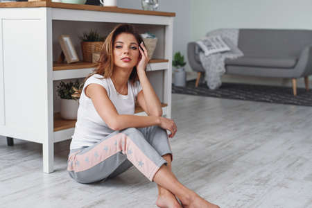 Cute young woman sits on the floor on the kitchen and enjoying the morning. Woman dressed in casual sportswear.