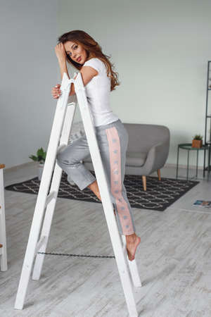 Positive beautiful young woman on a white wooden stepladder on the background of a stylish modern kitchen.