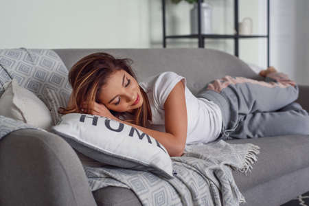 Pretty young woman with beautiful smile lies on grey couch with pillows at cozy home. Cute girl having rest at home in lazy day.