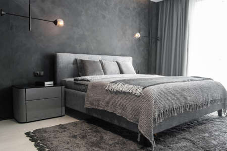 Master bedroom for a lonely stylish man, a bachelor. Modern room with trendy gray interiors, large king-size and lamps.