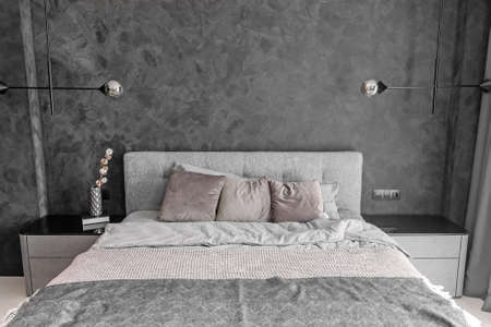 Grey bed in monochromatic bedroom with pillows and loft lamps on the wall. Stockfoto