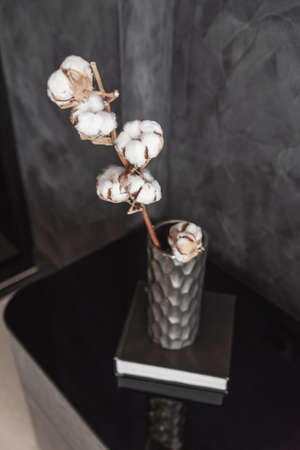 Dried cotton branch in stylish ceramic vase stands on black book and modern gret bedside table. Interior details. Stockfoto