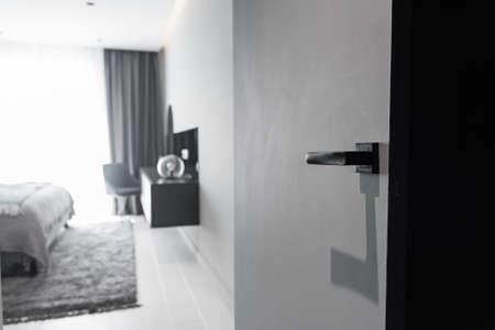 Modern black door handle and lock on black wooden hidden door. Close-up elements of the modern interior of the apartment.
