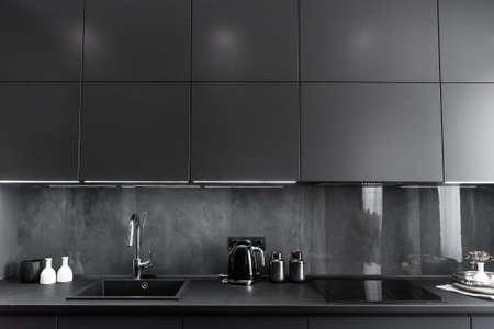 stylish kitchen interior in grey and black colors, black worktop and grey backsplash