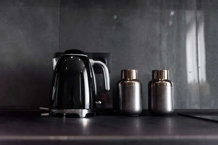 Modern black kettle and bottles for spices standing on black kitchen workspace on the background of grey tile like a marble.