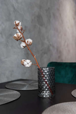 Dried cotton branch in stylish ceramic vase stands on black kitchen table. Interesting modern interior details. Grey wall background. Stockfoto
