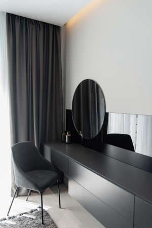 Womens make-up corner with chair, table and mirror in modern grey bedroom in stylish grey interior.