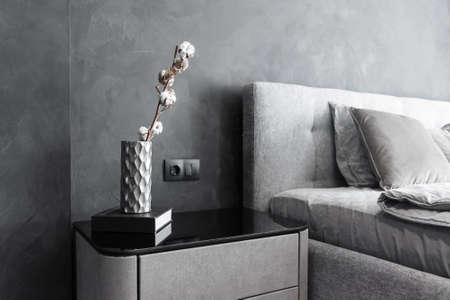 Stylish bedside table with dark book and vase with dried cotton branch on it. Interior details. Stockfoto