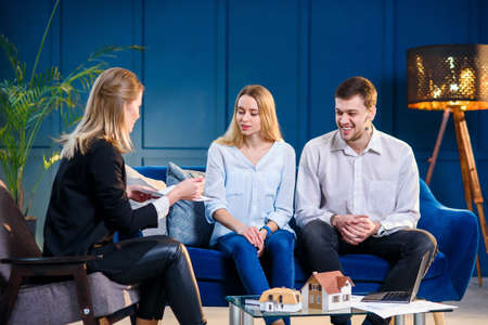 Caucasian young man and woman on the meeting with realtor, interior designer, decorator. Stockfoto