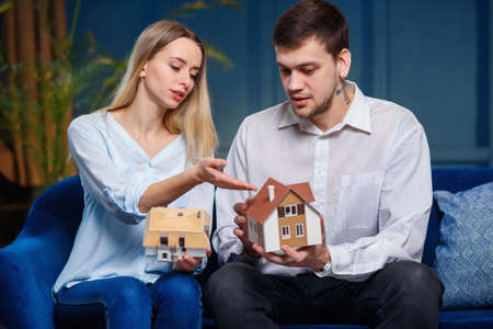Cute caucasian man and woman discussing two model of 3d maket of house. Stockfoto