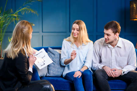 Young cute family on the meeting with realtor, interior designer, decorator. Stockfoto