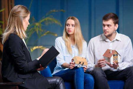Concentrated cute couple on the meeting with designer on the blue wall background. Stockfoto