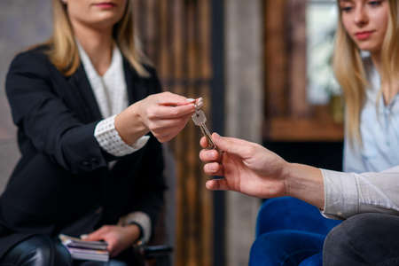 Stylish realtor with money on the hand giving key from flat, house to the young couple.