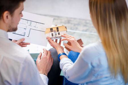 Caucasian man and woman discussing design of 3d model and sketch of future house.